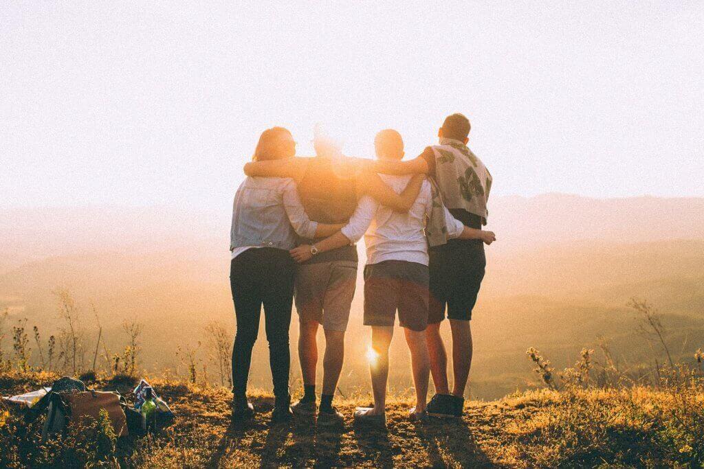Amigos abraçados no topo da montanha