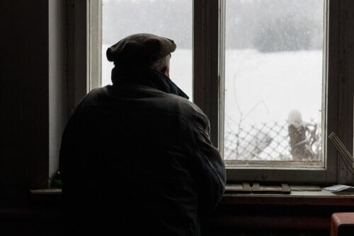 Idoso olhando pela janela com neve