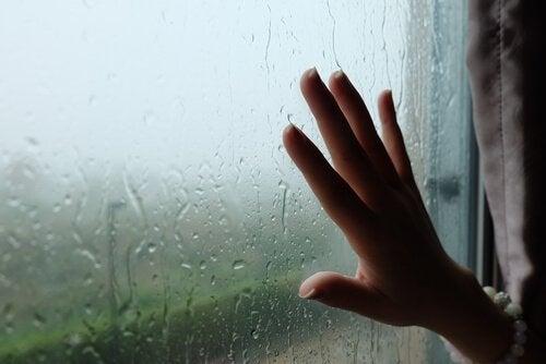 Mão na janela embaçada por chuva