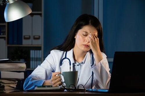 Médica exausta tomando café