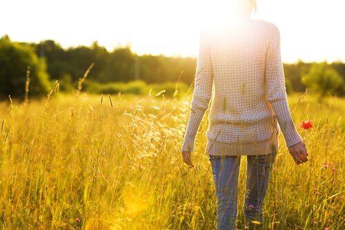 Mulher caminhando sob o sol