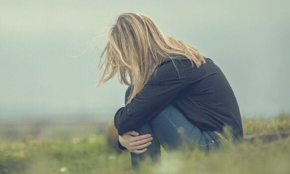 Mulher abaixada e triste