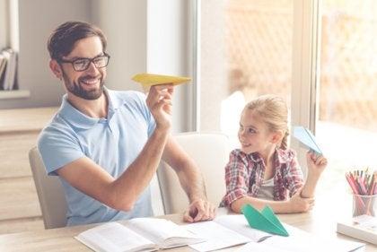 Pai e filha fazendo aviãozinho de papel