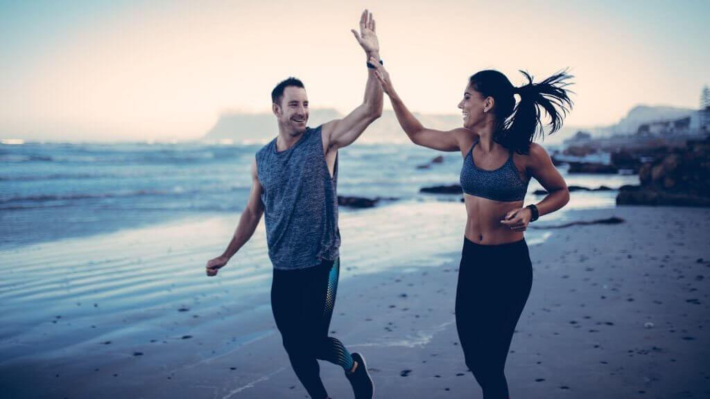 Casal correndo na praia