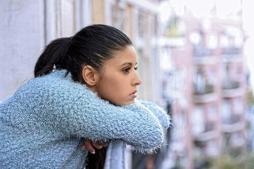 Mulher pensativa debruçada na varanda