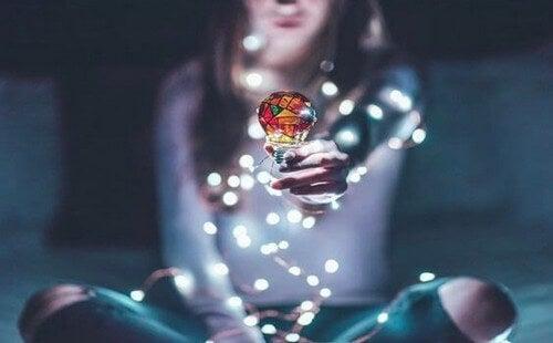Mulher segurando lâmpada colorida