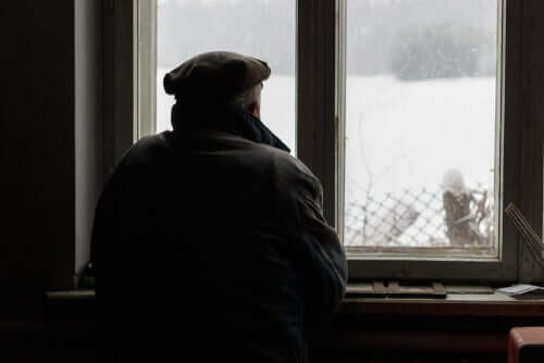 Homem idoso olhando pela janela