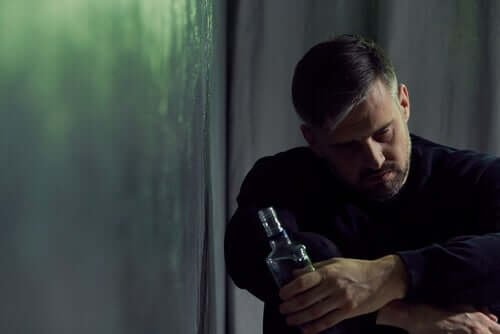 Homem com garrafa de bebida alcoólica na mão