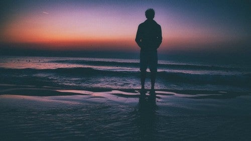 Homem na praia contemplando o horizonte