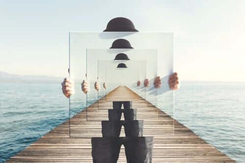 Homem segurando espelho representando o infinito