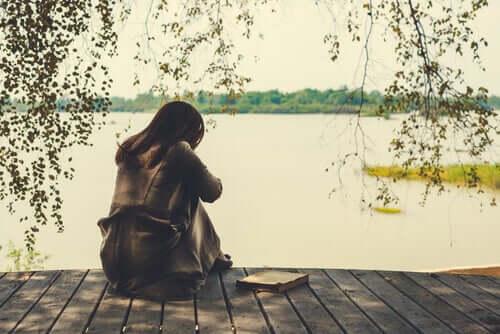 Mulher sozinha na beira de um lago