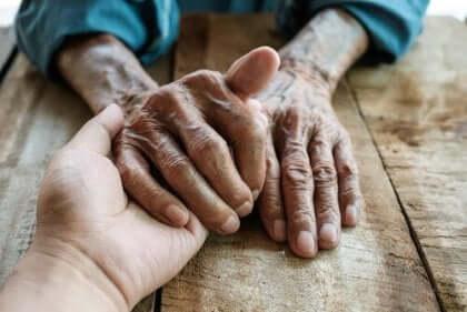 Adulto pegando na mão de um idoso
