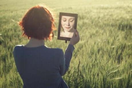 Garota se olhando em um espelho no campo