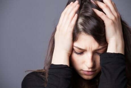 Garota preocupada com as mãos na cabeça