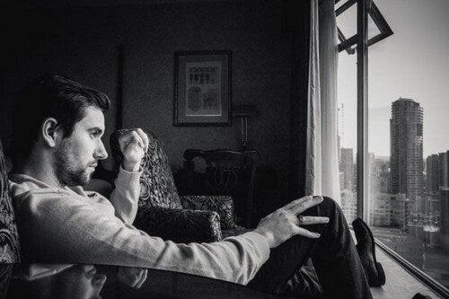 Homem sentado olhando pela janela