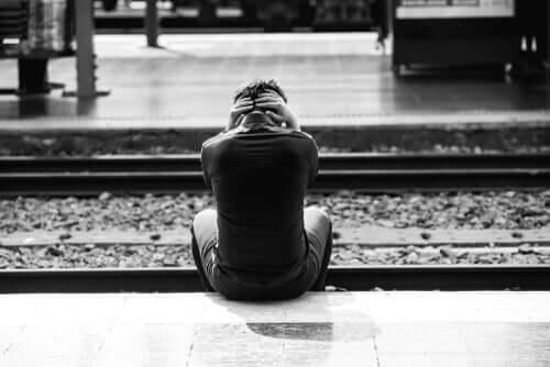 Homem sentado sozinho em trilho
