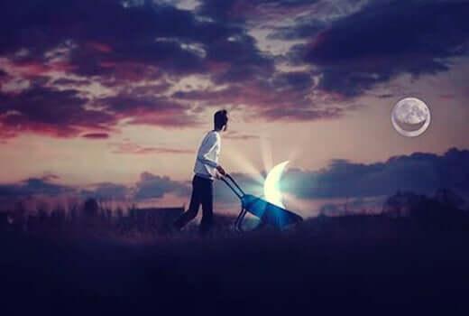 Homem carregando a lua em carrinho de mão