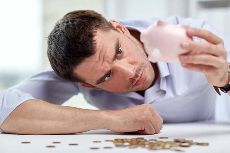Homem tirando moedas de cofrinho