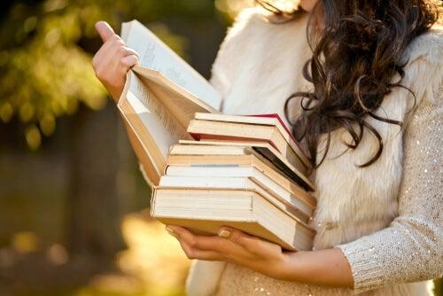 Mulher lendo livros ao ar livre