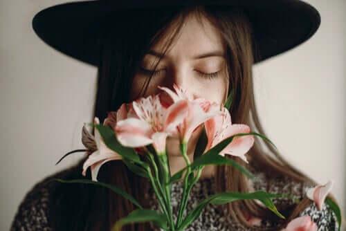 Mulher sentindo o aroma de flores