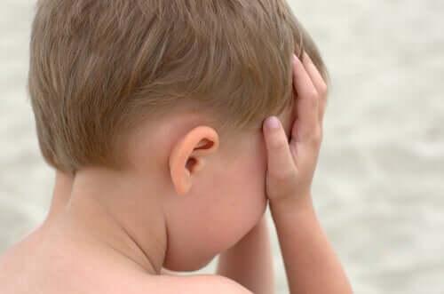 Criança com as mãos na cabeça