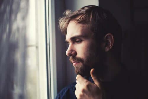 Homem pensativo olhando pela janela