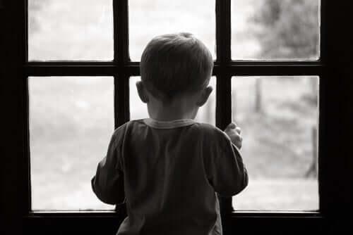 Criança triste diante de janela