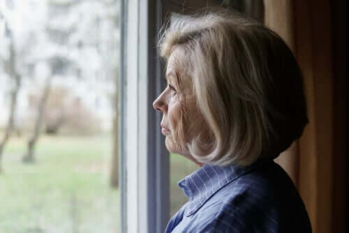 Senhora idosa olhando pela janela