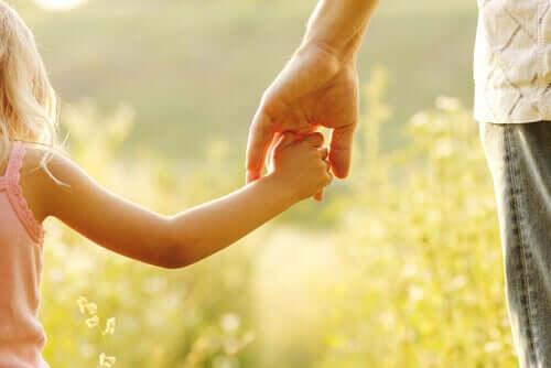 Criança de mão dada com adulto