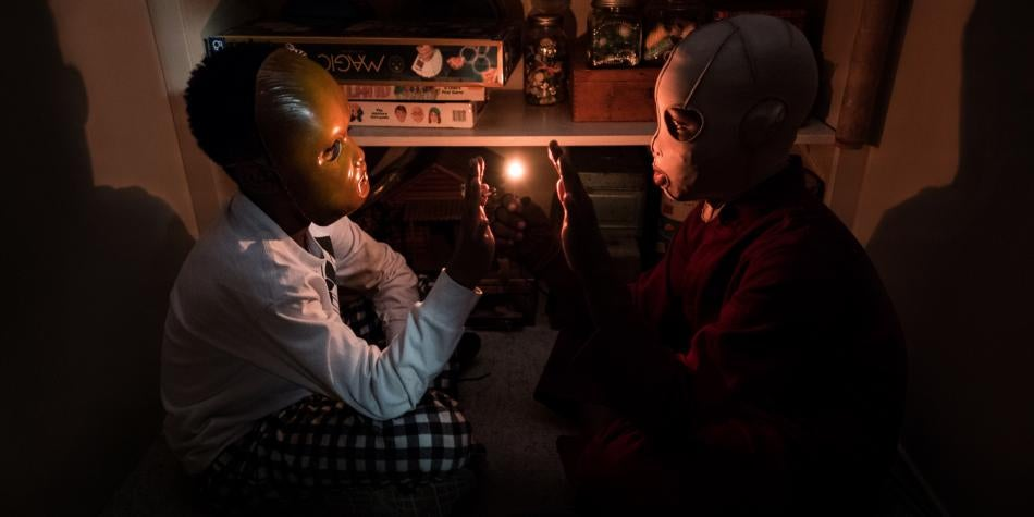 Duas crianças com máscaras no escuro