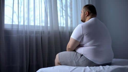 Homem obeso sentado em sua cama