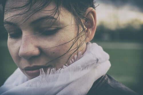 Mulher com os cabelos ao vento pensando na felicidade