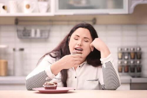 Mulher comendo doce em casa