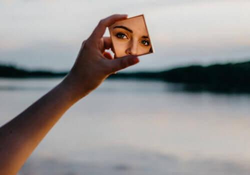 Mulher se olhando em espelho pequeno