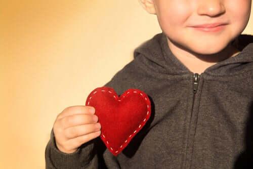 Menino segurando um coração de tecido