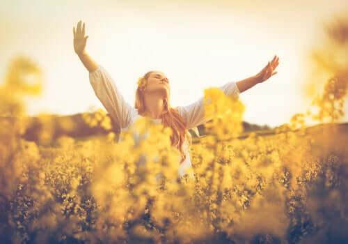 Menina abrindo os braços no campo