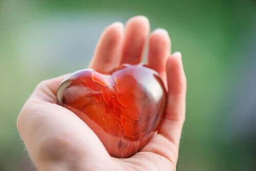 Mão segurando coração de vidro