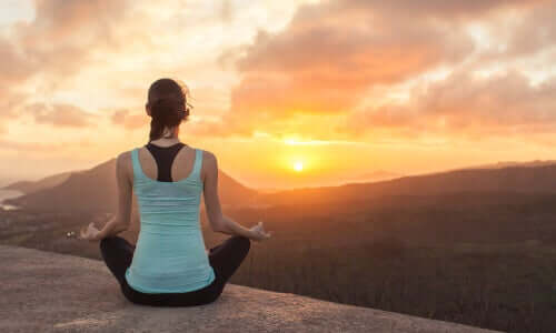 Garota meditando em cima de montanha