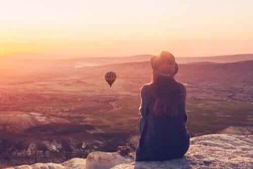 Garota vendo balões em cima de uma montanha