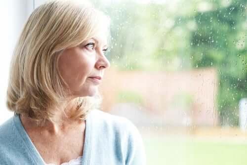 Mulher madura olhando pela janela