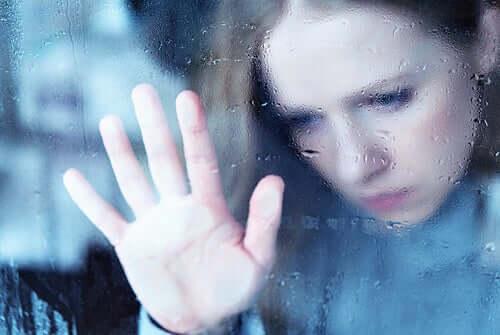 Mulher triste com a mão na janela