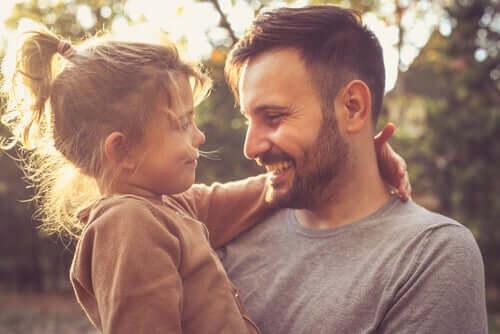 Pai sorrindo com filha no colo