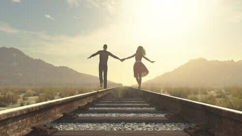 Casal andando no trilho do trem
