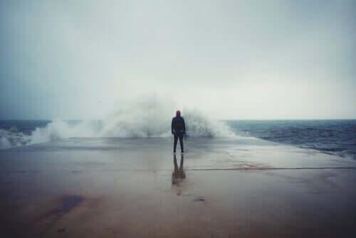 Homem diante de mar revolto