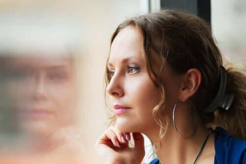 Mulher pensativa encostada em janela