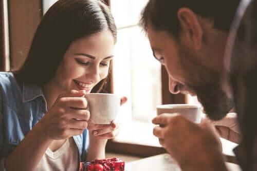 Casal sorrindo tomando café
