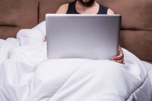 Homem vendo pornografia na cama