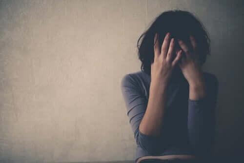 Mulher em depressão cobrindo seu rosto