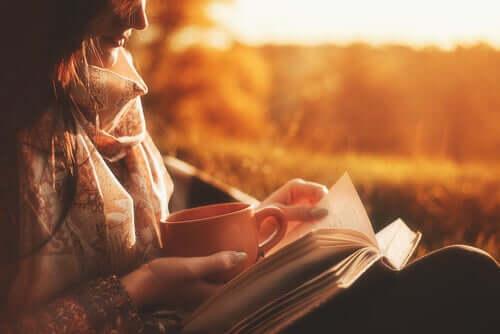 Mulher lendo um livro e tomando um café