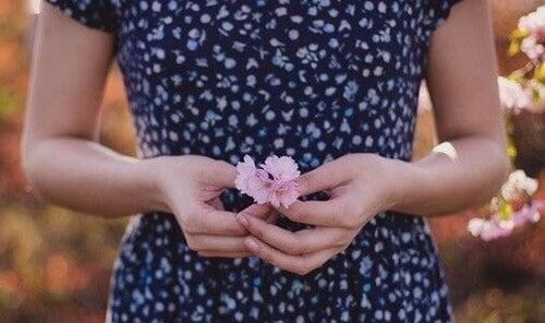 Mulher segurando flor cor-de-rosa